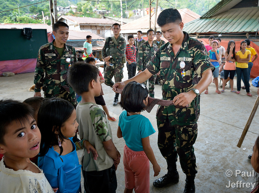 Soldiers of the Armed Forces of the Philippines play games with children in Diwalwal, a remote mining community on the Philippines' southern island of Mindanao. Also known as Mt. Diwata, the community has become the center of an international struggle between small scale miners and large international mining corporations. The military has been ordered by the government to protect the interests of the large mining companies, and frequently engages in repression and harassment of opponents of large scale mining. To improve its image in the community, soldiers have been carrying out civil assistance missions such as this in an effort to win hearts and minds among residents of poor communities..