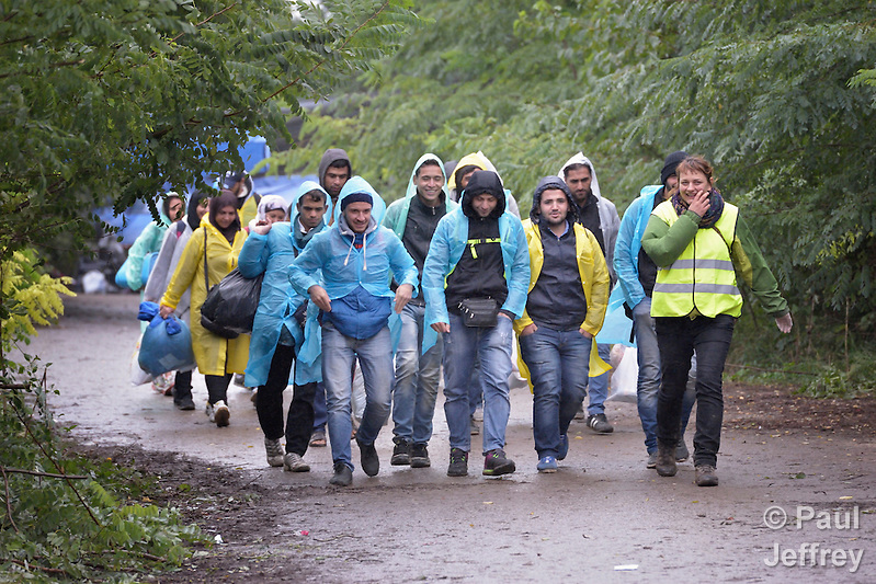 Escorted by a Czech volunteer (in the yellow vest), refugees approach the border into Croatia near the Serbian village of Berkasovo. Hundreds of thousands of refugees and migrants from Syria, Iraq and other countries have flowed through Serbia in 2015, on their way to western Europe. (Paul Jeffrey)