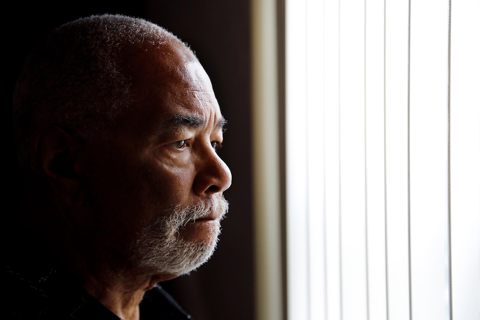 "James Piggee, 75, looks out a window towards his neighbor's house in his Des Moines home. He has felt more confined to his home over the last 20 years than he would prefer.  Gay and living with his partner of 53 years, Piggee has received threats and intimidation from his next door neighbors, James Anthony Mullins and Raulyn Walker.  Police reports state his neighbors have ""called them 'bitches, faggots and threatened to kick their f------ a-s.' ""  Piggee question how Mullins especially can continue to receive subsidized housing from the city in spite of a criminal record. (Christopher Gannon/The Register)"