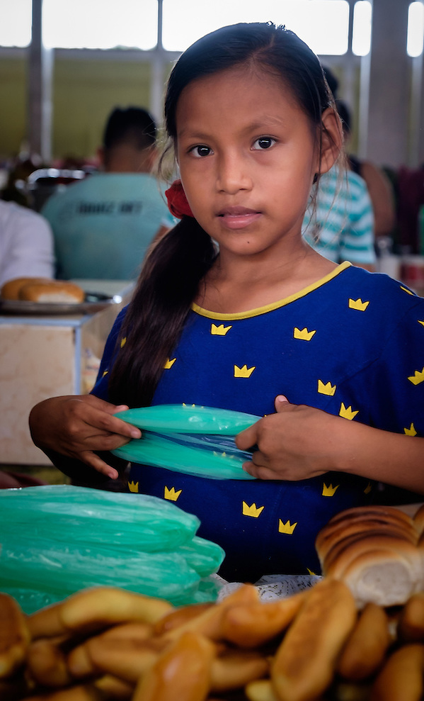NAUTA, PERU - CIRCA OCTOBER 2015: Girl selling bread in Nauta market in the Peruvian Amazon (Daniel Korzeniewski)