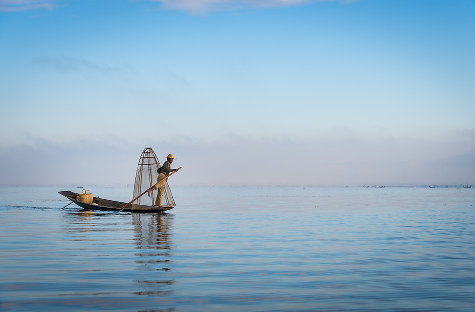 INLE LAKE, MYANMAR - CIRCA DECEMBER 2013: Fisherman rowing a typical boat in the Inle Lake, Myanmar (Daniel Korzeniewski)