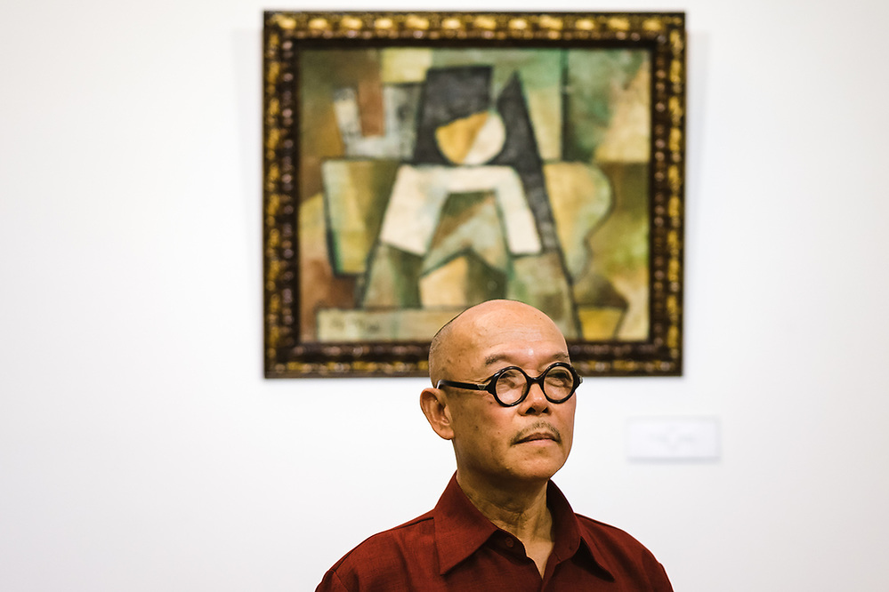 "HO CHI MINH CITY, VIETNAM – JULY 18, 2016: A portrait of Vietnamese artist Thanh Chung with his painting, ""The Abstract,"" which he says he created in the 1970's. The piece, part of exhibition in Ho Chi Minh City, Thanh Chung says, was altered, reattributed to another well-known Vietnamese artist and dated decades before he created it. (Quinn Ryan Mattingly)"