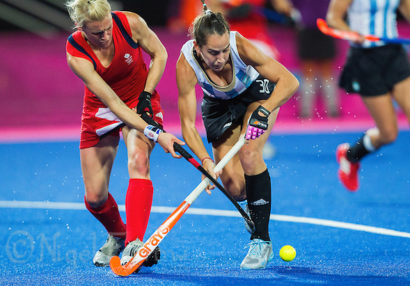 08 AUG 2012 - LONDON, GBR - Alex Danson (GBR) of Great Britain (left) and Josefina Sruoga (ARG) of Argentina (right) compete for the ball during the London 2012 Olympic Games women's semi final match between the two teams at the Riverbank Arena in the Olympic Park, Stratford, London, Great Britain .(PHOTO (C) 2012 NIGEL FARROW) (NIGEL FARROW/(C) 2012 NIGEL FARROW)