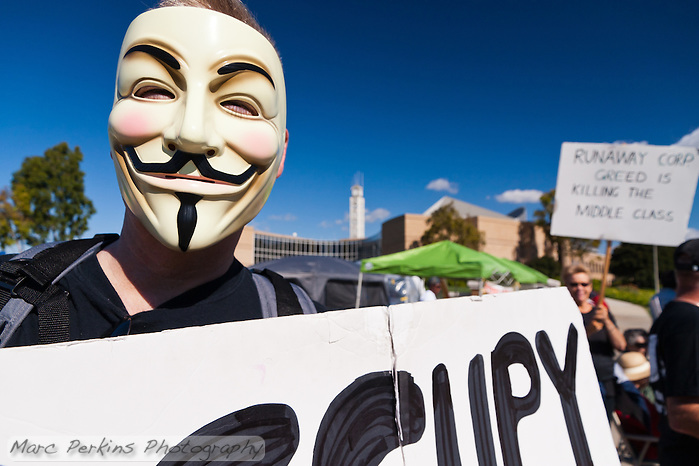 "Ted holds an ""Occupy OC"" sign while wearing a Guy Fawkes mask at the Occupy Orange County, Irvine camp on November 5.  Behind him is the Irvine Civic Center and a woman holding a ""Runaway corp. greed is killing the middle class."" sign. (Marc C. Perkins)"