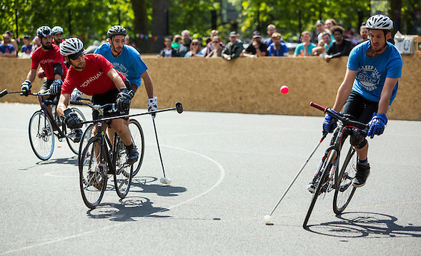 17 AUG 2014 - LONDON, GBR - A player from Mondial (in red and black) shoots in his teams game against Sentinels (in blue) at the 2014 London Open bike polo tournament in Highbury Fields in London, Great Britain (PHOTO COPYRIGHT © 2014 NIGEL FARROW, ALL RIGHTS RESERVED) (NIGEL FARROW/COPYRIGHT © 2014 NIGEL FARROW : www.nigelfarrow.com)
