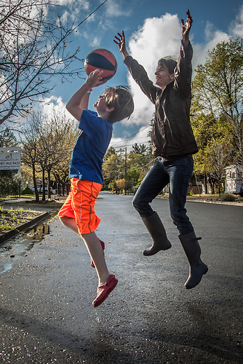 Anna Johansson and her son Leonardo play a little one-on-one during a break in the rain in front of their house on Cedar Street in Calistoga (Clark James Mishler)