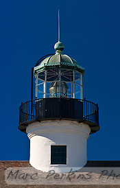 A head-on look at the lantern room and lens of Old Point Loma Light, seen from the east.  The window visible in the lantern tower is the one visitor's can look out when they climb the lighthouse stairs.  The lighthouse's green (copper) roof is clearly visible, with its beautiful cut-out wave edging visible.  The shingle roof of the lighthouse's main building is visible at the bottom of the picture.  The lighthouse is in Cabrillo National Monument near San Diego, CA. (Marc C. Perkins)