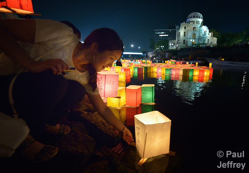 A woman sets a floating candle lantern on the river on August 6, 2015, in Hiroshima, Japan. The lanterns, thousands of which were launched on the 70th anniversary of the atomic bombing of the city, carried handmade messages and drawings, conveying each person's prayers for peace and comfort for the victims of the violence. In the background are the ruins of a building damaged by the bomb and now converted into a peace memorial. (Paul Jeffrey)