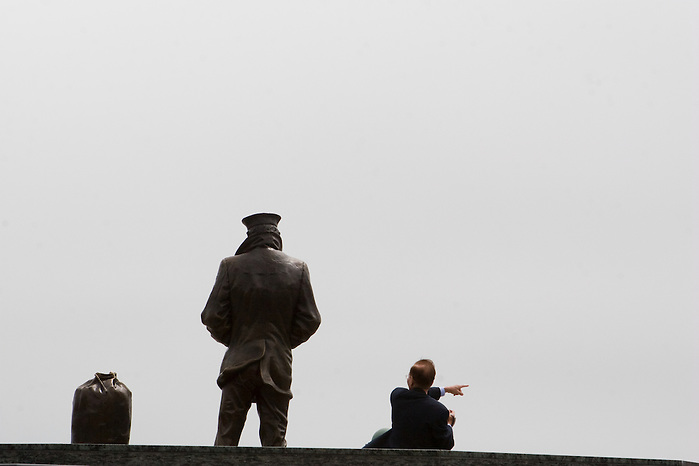 Asian tourist interacting with the Lone Sailor's Memorial in Golden Gate Park, San Francisco California. (Kathryn Wagner)