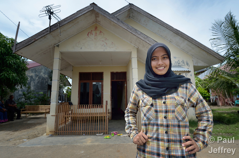 Nurul Aina stands in front of a home she owns in the Lam Pulo neighborhood of Banda Aceh, Indonesia. She was just 8 years old in 2004 when a massive tsunami swept over the city, killing her parents and two siblings and leveling their home. Aina was fortunately visiting relatives in a neighborhood far from the seashore when the tsunami hit. With assistance from the Katahati Institute and Diakonie Katastrophenhilfe, a new house was built and titled in Aina's name, an accomplishment that required considerable legal advocacy by Katahati staff. As a result, rental income from the house has paid for Aina's schooling while she lives with her grandmother. Now 18, Aina is studying English at a local university, and plans to move into her house some day. The tsunami killed 221,000 people in Aceh province and left more than 500,000 displaced. (Paul Jeffrey)