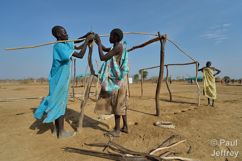 Women construct a shelter in the internally displaced persons camp in Turalei, South Sudan. Families started arriving here shortly after fighting broke out in December 2013, and new families continued to arrive in March 2014 as fighting continued. Many are living in the open and under trees. The ACT Alliance is providing the displaced families and the host communities affected by their presence with a variety of support, including new wells. (Paul Jeffrey)