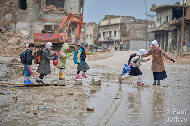 Girls navigate a muddy street as they make their way to school amid the rubble of the Old City of Mosul, Iraq, which was devastated during the 2017 Battle of Mosul, which led to the defeat of the Islamic State group, also known as ISIS. During control of the city by the Islamic State, most children didn't attend school. (Paul Jeffrey)