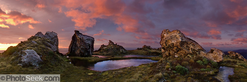 "Sunrise illuminates the curious tors and tarns (crags and ponds) on Hump Ridge, a track (trail) for trampers (hikers and trekkers) in Fiordland National Park, South Island, New Zealand. In 1990, UNESCO honored Te Wahipounamu - South West New Zealand as a World Heritage Area. Published in ""Light Travel: Photography on the Go"" book by Tom Dempsey 2009, 2010. Panorama stitched from 5 overlapping images. (© Tom Dempsey / PhotoSeek.com)"