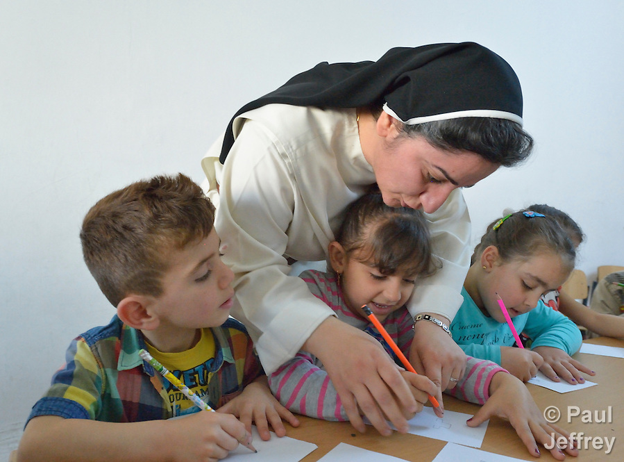 Sister Ferdos Zora helps a student draw in a preschool for displaced children run by the Dominican Sisters of St. Catherine of Siena in Ankawa, near Erbil, Iraq. The children, and the nuns themselves, were displaced by ISIS from Mosul and Qaraqosh in 2014. The sisters have established a variety of schools and other ministries among the displaced. (Paul Jeffrey)