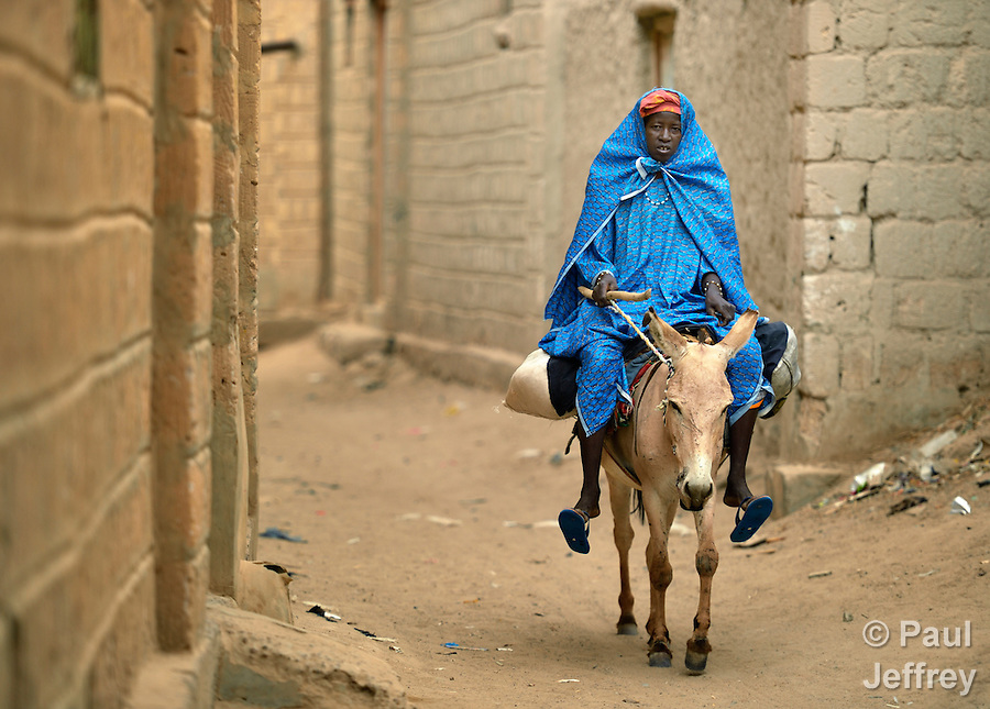 A woman rides a donkey in Timbuktu, a city in northern Mali which was seized by Islamist fighters in 2012 and then liberated by French and Malian soldiers in early 2013. (Paul Jeffrey)