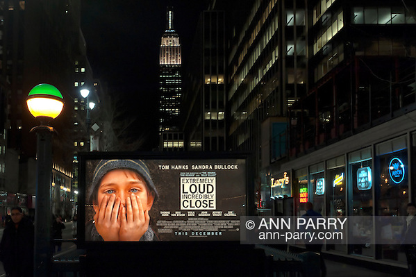"Manhattan, NY, USA - January 9, 2012: Movie poster ""Extremely Loud & Incredibly Close"" hangs illuminated at night over Penn Station subway entrance with Empire State Building in background. Fictional movie is set at time of 9/11 terrorist attacks on Twin Towers in NYC. Green and yellow lit globe on post is at stairwell entrance to MTA (Metropolitan Transit Authority) 34 St. Penn Station subway station. (Ann E Parry/Ann Parry, ann-parry.com)"