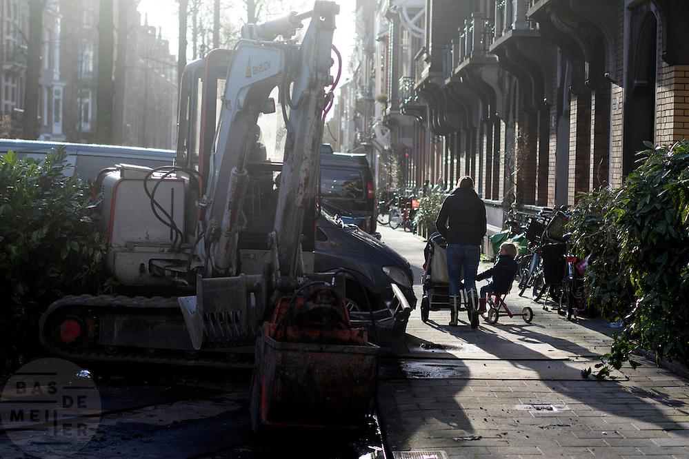 In Amsterdam loopt een vrouw met een wandelwagen en een jongetje op een driewieler langs een graafmachine.