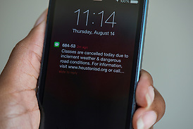 An emergency text is displayed on a smartphone, August 14, 2014. (Houston ISD/Dave Einsel)