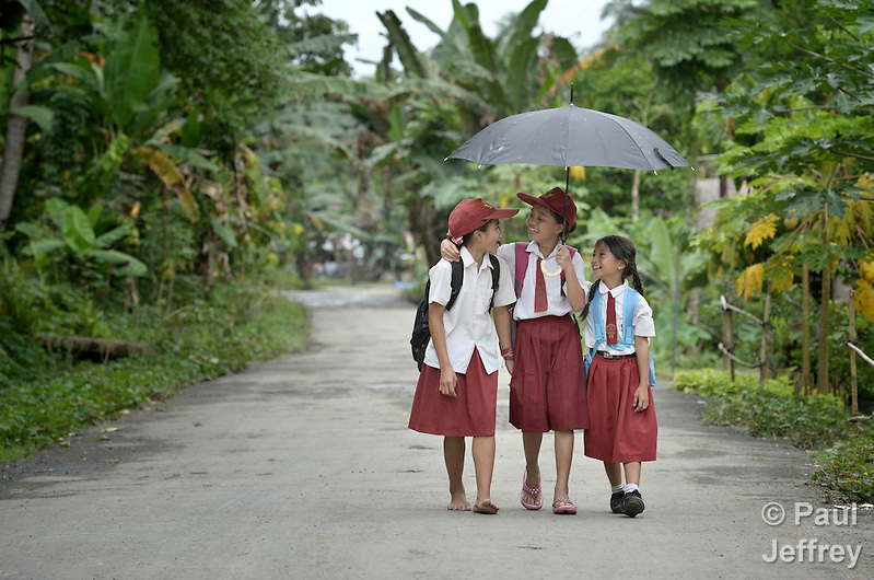 "Three girls walk to school in Tugala, a village on the Indonesian island of Nias. The village was struck by both a 2004 tsunami and a 2005 earthquake, leaving houses destroyed and lives disrupted. The ACT Alliance helped villagers here to construct new homes and latrines, build a potable water system, open a clinic and schools and get their lives going once again. For the residents of Tugala, the post-disaster mantra of ""build back better"" became a reality with help from the ACT Alliance. (Paul Jeffrey)"