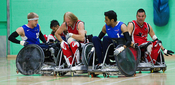 15 AUG 2011 - LEEDS, GBR - Canada's Garett Hickling (centre) holds onto the ball as he attempts to avoid a challenge from Great Britain's Aaron Phipps (left) and Mandip Sehmi during the wheelchair rugby exhibition match between the two teams .(PHOTO (C) NIGEL FARROW) (NIGEL FARROW/(C) 2011 NIGEL FARROW)