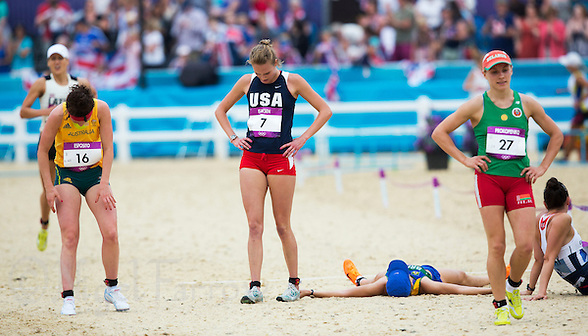 12 AUG 2012 - LONDON, GBR - Margaux Isaksen (USA) (centre in blue and red) of the USA recovers after finishing fourth overall in the women's London 2012 Olympic Games Modern Pentathlon in Greenwich Park, Greenwich, London, Great Britain .(PHOTO (C) 2012 NIGEL FARROW) (NIGEL FARROW/(C) 2012 NIGEL FARROW)
