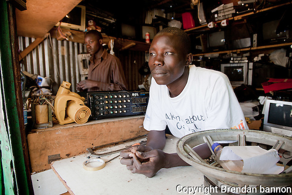 """I see the momentum of my business building quickly, soon you will find me in a modern structure as my shop,"" said Peter Ogweno (R) , 32. He opened his electronics repair shop in Nairobi's Kibera slum in 2008 after working as an apprentice at a competitor's shop. (brendan bannon)"