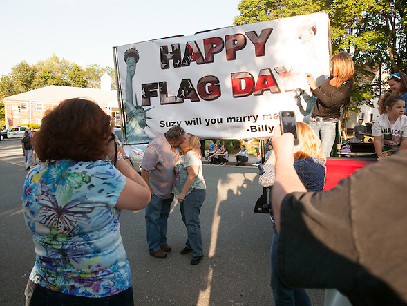 Dedham, MA 06/14/2013 Susan Roche and Bill Guilfoyle kiss after Guilfoyle proposed with a sign carried on the back of a truck in the Dedham Flag Day Parade on Friday evening. Wicked Local Photo by Alex Jones (Alex Jones/Wicked Local Photo by Alex Jones)