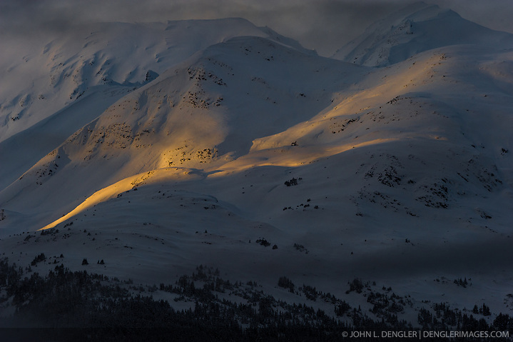 A sliver of an early morning sunrise shines on  the slopes of Mount Jonathan Ward outside Haines, Alaska near the Alaska Chilkat Bald Eagle Preserve. (John L. Dengler)