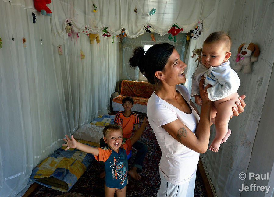 A Roma woman holds her baby inside a shipping container that has been converted into a house in Makis, a village outside of Belgrade, Serbia. These Roma families were evicted from an urban squatter settlement in 2012 to make way for construction of new apartments and office buildings. The shipping containers they now call home, which were provided at no cost by local authorities, are far from the city center. (Paul Jeffrey)