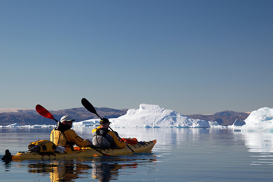 Sea kayakers paddling among icebergs on Sermilik Fjord near settlement of Tiniteqilaq, East Greenland (Brad Mitchell)