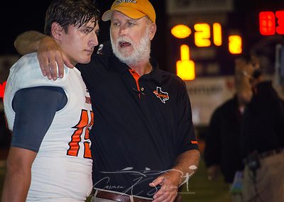Refugio High School head football coach Jason Herring talks to quarterback Jared Kelley, Sept. 29, 2017, in Seguin, Texas. The team lost to Navarro High School 21-17, bringing their record to 2-1. Many of the team members have been sleeping in the team's weight room after their homes were destroyed by Hurricane Harvey in late August. (Photo by Carmen K. Sisson) (Carmen K. Sisson/Cloudybright)
