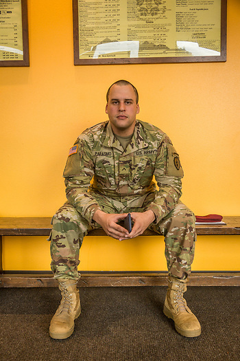 """I'm six months in the Army, one month in Alaska and I have six jumps under my belt.""  -PV-2 Army 19 Delta Calvery Scout Marcelo Parasmo awaits friends at Middle Way Cafe in Anchorage, Alaska. (Clark James Mishler)"