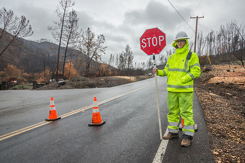 Traffic Control Supervisor Jake Brown stops traffic while crews work to stabilize areas along Hwy. 128 between Calistoga and Winters, CA. (Clark James Mishler)