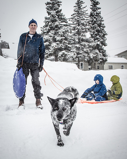 Ian Rhude with sons and dog during a late winter snow storm, South Addition, Anchorage (Clark James Mishler)