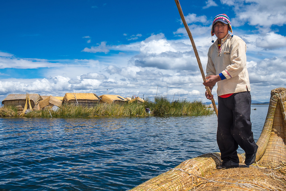 UROS ISLANDS, PERU - CIRCA APRIL 2014: Man from the Uros Islands in Lake Titicaca rowing in typical canoe made of totora reeds. (Daniel Korzeniewski)