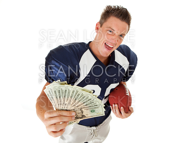 Caucasian American football player, in uniform, isolated on white, with various related props. (Sean Locke/copyright Sean Locke @ seanlockephotography.com)