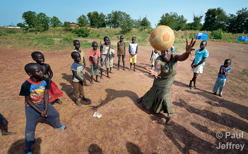 Children practice volleyball skills inside a camp for internally displaced families in Yei, South Sudan. The camp holds Nuer families who took refuge there in December 2013 after a political dispute within the country's ruling party quickly fractured the young nation along ethnic and tribal lines. The ACT Alliance is providing psycho-social services in the camp, including safe places for children to enjoy being children. Chasing the ball is Victoria Amude, program manager of children's protective services for the Institute for the Promotion of Civil Society, whose work in the camp is funded by ICCO, a member of the ACT Alliance. (Paul Jeffrey)