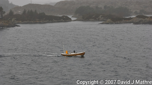 Fisherman on a foggy morning in a small boat getting out of the way. Image taken with a Nikon D2xs camera and 28-70 mm f/2.8 lens (ISO 400, 70 mm, f/6.3, 1/160 sec). (David J Mathre)