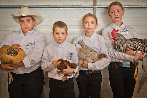 4H kids, Calbe Glaser, Aidan Siegel, Isabella Siegel, and Jaida Vroman with their poulty prize winning entries at the Alaska State Fair, Palmer, Alaska (Clark James Mishler)