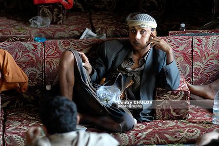 "Le Conde qat chewing cafe client consuming qat. Sanaa, Yemen. Qat, also known as Khat (Catha edulis) is a large, slow growing, evergreen shrub, reaching a height of between 1 and 6 meters, in equatorial regions it may reach a height of 10 meters. This plant is widely cultivated in Yemen and is generally used for chewing. When Khat juice is swallowed, its leaf juice has a caffeine-like effect. It is deeply rooted in Yemeni culture, which it has exported to its neighbours across the Gulf of Aden, Somalia, Djibouti and, to a lesser degree, Eritrea (where it is mainly consumed by ethnic Arabs of Yemeni and Rashaida origins). Khat is chewed by men and women. In European Union and many other countries qat is considered a forbidden narcotic. Клиент кафе для жевания ката ""Ле Конде"" в столице Йемене г. Санаа. Кат (Catha edulis) – это высокий, медленно растущий, вечнозеленый кустарник, достигающий высоты от 1 до 6 метров, в экваториальных районах выростающий до 10 метров. Это растение широко культивируется в Йемене, его листья используют для жевания. Смешавшись со слюной при жевании сок ката производит эффект, подобный эффекту кофеина. Жевание ката – давняя национальная культурная традиция в Йемене, со временем распространившаяся за его границы через Аденский залив в Сомали и Джибути, в меньшей степени – в Эритрею. Кат жуют и женщины и мужчины. В Европейском Союзе и многих других странах кат считается запрещенным наркотиком. (Dmitry Chulov)"