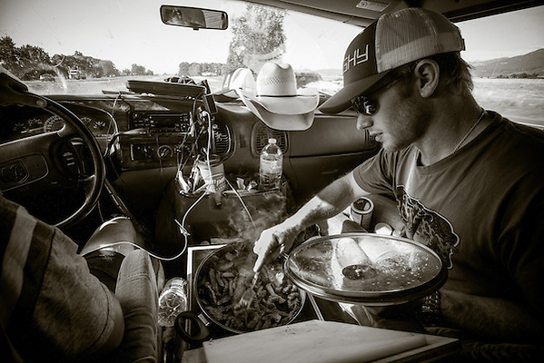 Jacobs Crawley cooks dinner for 3 fellow saddle bronc riders as their van heads up I-5 near Salem, Oregon. (Darren Carroll)
