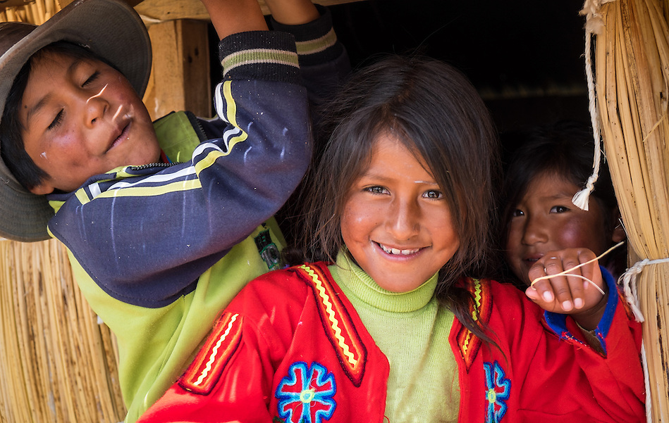 UROS ISLANDS, PERU - CIRCA APRIL 2014: Kids brothers from Uros Islands in Lake Titicaca, in from of their traditional hut. (Daniel Korzeniewski)