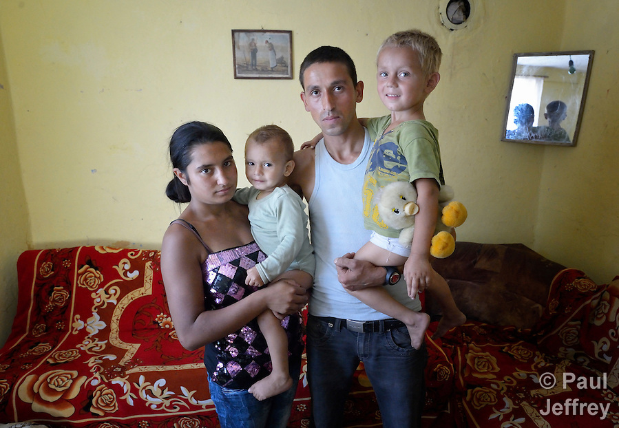 Feride Ramadan Mehmed (left) and her husband Mehmed hold their children Birdzhan, 1, and Erdzhan, 3, in their house in the Maxsuda neighborhood of Varna, Bulgaria. They are Turkish-speaking Roma, and were violently driven out of one neighborhood by racist gangs. They took refuge in a United Methodist Church for a year before finding this small house to rent. (Paul Jeffrey)