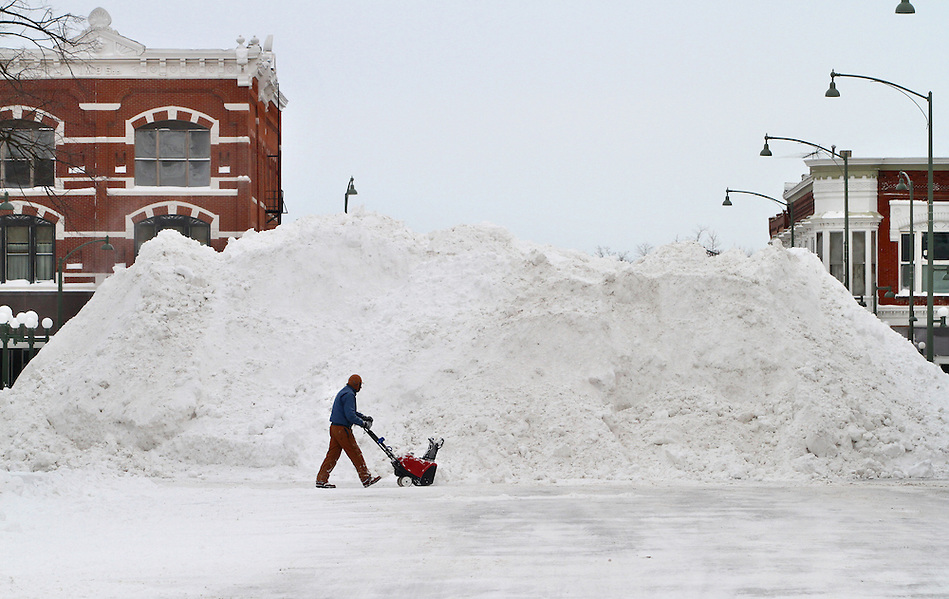 While helping the city dig out from heavy snowfall, Ed Dieleman walks past a 20-foot heap of snow in the town square of Oskaloosa, Iowa on Wednesday, February 2, 2011.  Many Oskaloosa residents are saying the heaps are the largest they've ever seen. (Christopher Gannon/The Register)