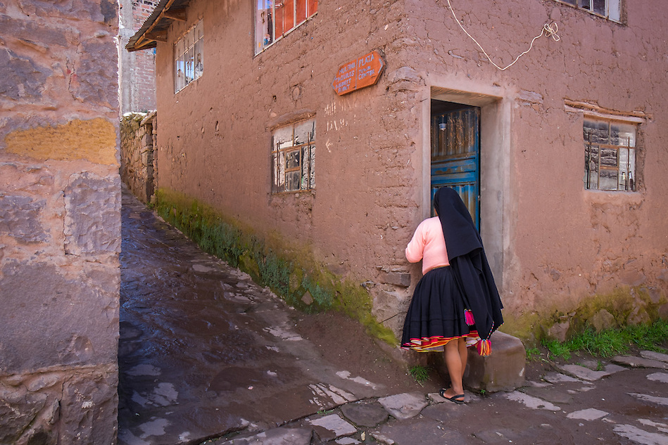 TAQUILE ISLAND, PERU - CIRCA APRIL 2014: Woman in typical street in of Taquile Island, in Lake Titicaca, Peru. (Daniel Korzeniewski)