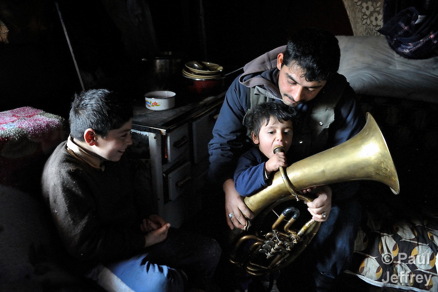 "THIS PHOTO IS AVAILABLE AS A PRINT OR FOR PERSONAL USE. CLICK ON ""ADD TO CART"" TO SEE PRICING OPTIONS.   Milan Pesic gets help from one of his children as he practices his french horn inside his home in a Roma settlement in Belgrade, Serbia. He plays in a Roma band. The families that live here, many of whom survive from recycling cardboard and other materials, are under constant threat of eviction in order to make way for new high-rise office buildings. (Paul Jeffrey)"