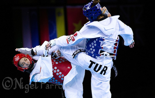 10 AUG 2012 - LONDON, GBR - Hwang Kyung-Seon (KOR) (left) of South Korea and Nur Tatar (TUR) (right) of Turkey both land kicks during the women's -67kg category final at the London 2012 Olympic Games Taekwondo at Excel in London, Great Britain .(PHOTO (C) 2012 NIGEL FARROW) (NIGEL FARROW/(C) 2012 NIGEL FARROW)