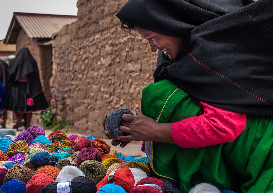 TAQUILE, PERU - CIRCA OCTOBER 2015: A woman from the insland of Taquile buying wool in the market of Taquile in Lake Titicaca. (Daniel Korzeniewski)