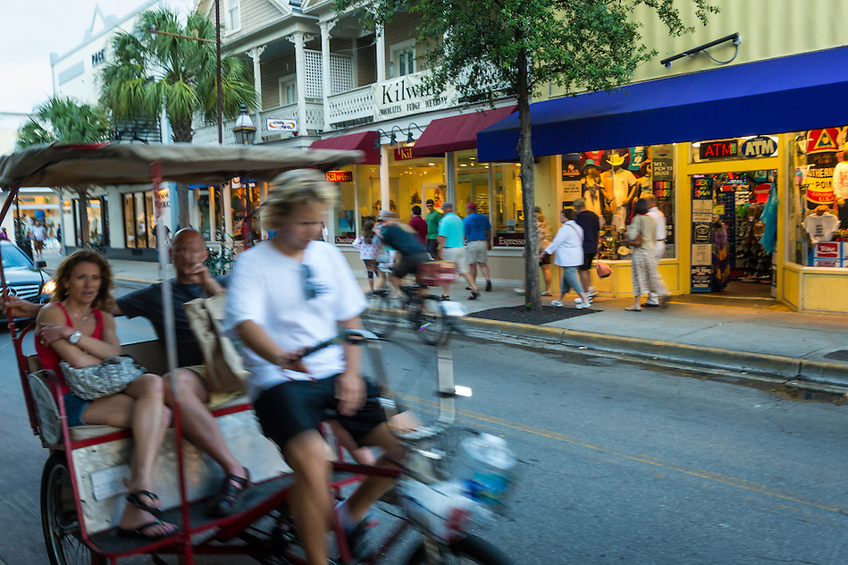 KEY WEST, FL - CIRCA 2012: Tourists in a Ricksaw in Duval Street in Key West circa 2012. The tropical city is a popular tourist destination with over 2 million yearly visitors. (Daniel Korzeniewski)