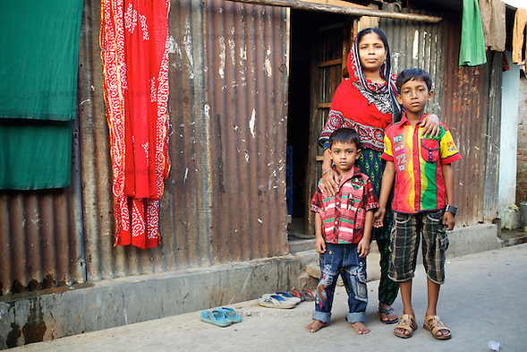 "Jahanara with her two sons Jahidul Islam, age 9 and Jahirul Islam, age 5, outside their home in 36 Bari Colony. Jahanara works as a tailor to supplement her husband's income as a construction worker. She volunteers for NGO forum as a health and hygiene promoter working with female adolescents in the slum. A passionate advocate of hand-washing to both adults and children, she's seeing the result of her efforts: ""I like doing the work that I do, the fact that people can stay healthy. I like the result of my work."" She's also involved in promoting drain clearing. ""Before, the latrines and drains were very dirty. Now, it's a lot better but there's so much more to do."" Jahanara Akhter, age 27, is a resident of 36 Bari Colony, a slum in Mymensingh. Oxfam are working with partners NGO Forum to support residents of 36 Bari Colony in health promotion and disaster preparedness. Photo: Tom Pietrasik Mymensingh, Bangladesh November 20th 2014 (Tom Pietrasik)"